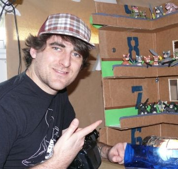animator lee hardcastle poses with the set from his Claycat's The Raid short film