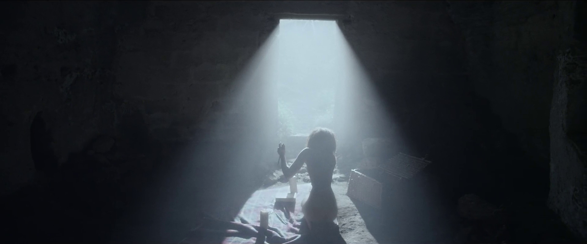 Louise sits naked in a shaft of natural light, about to kill a rabbit to save her derteriorating body