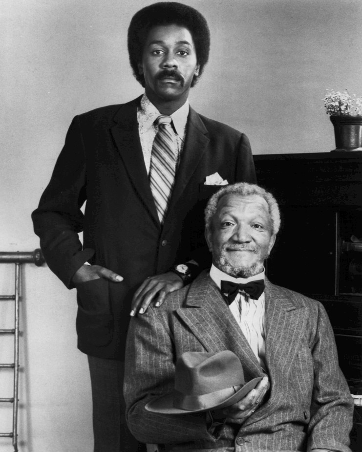 Redd Foxx and Desmond Wilson pose next to a piano in a beautiful black and white photograph