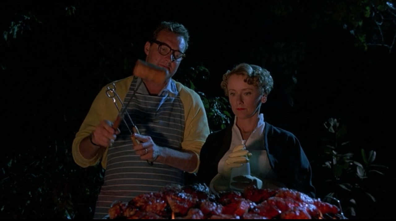 Randy Quaid and Mary Beth Hurt stand over a grill almost overflowing with meat