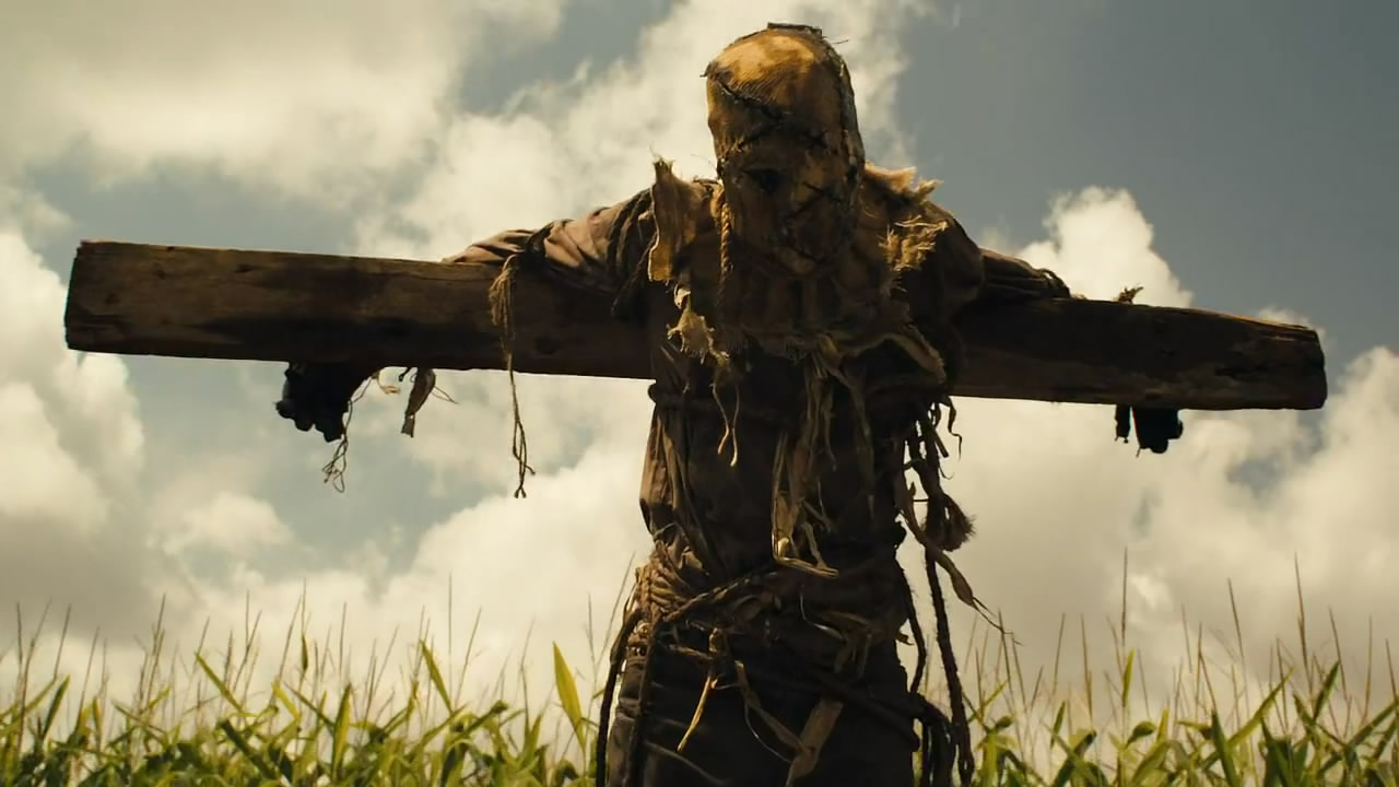 A particularly creepy looking scarecrow hangs ominously over a field of corn