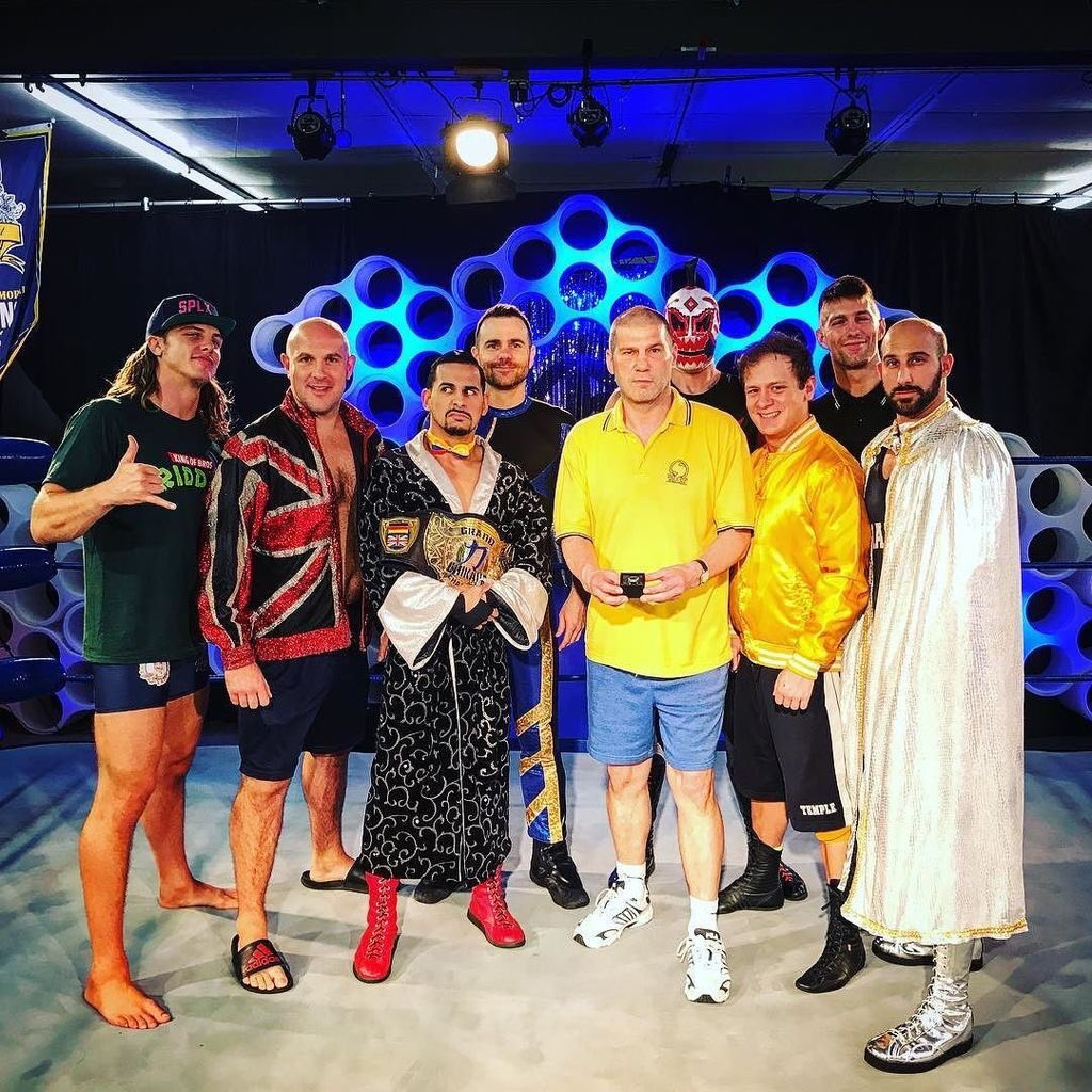 British pro wrestling legend Johnny Kidd stands in the ring with the entrants in the Invitational tournament from left to right: Matt Riddle, James Mason, Juan Francisco De Coronado, Mike Quackenbush, Hallowicked, Travis Huckabee, Zack Sabre Jr. and Rory Gulak