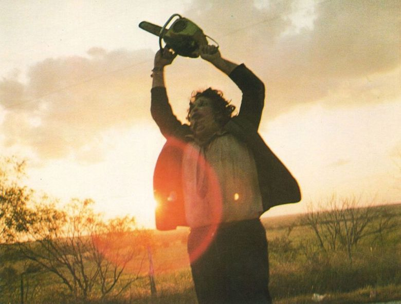 A still from The Texas Chainsaw Massacre from the closing scene as Leatherface swings his chainsaw high into the air as the sun rises behind him. He has a ragged mask made of human skin, with a dress shirt, tie and jacket