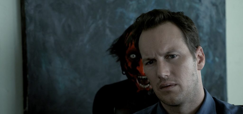 Josh Lambert, played by Patrick Wilson, looks into the distance as the terrifying Lipstick Faced Demon played by Joseph Bishara looms behind him