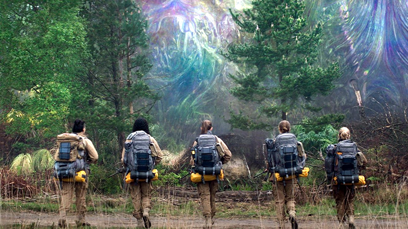 The main characters from Annhilation all stand in military gear walking away from the camera towards a mysterious multi-colored field that looms between trees on the edge of a forest