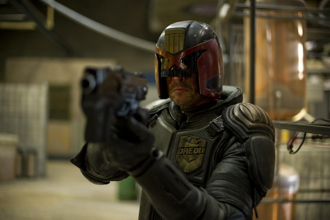 A battered and bruised Judge Dredd (Karl Urban) sternly points his gun at a target offscreen