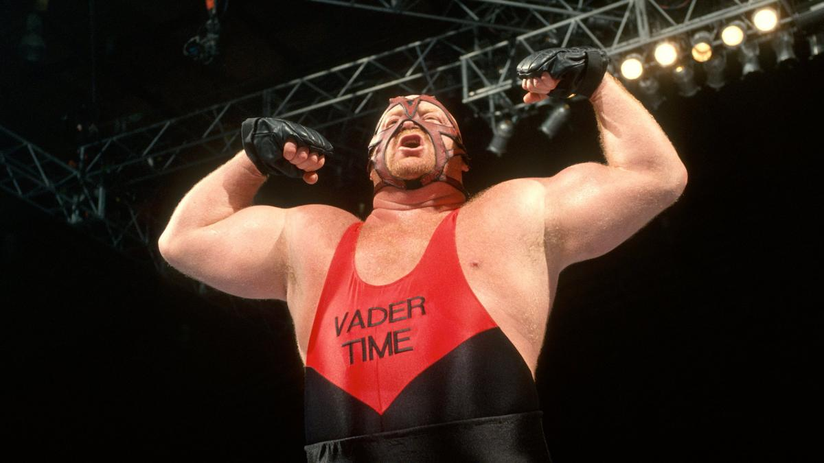 Leon White, also known as Big Van Vader poses in his singlet and facial mask performing a huge muscle pose.